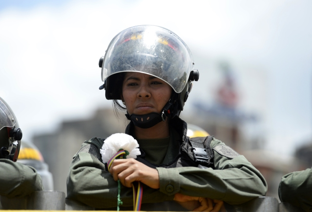 A Venezuelan Bolivarian NAtional Guard member holds a flower during a women's march aimed to keep pressure on President Nicolas Maduro, whose authority is being increasingly challenged by protests and deadly unrest, in Caracas on May 6, 2017. The death toll since April, when the protests intensified after Maduro's administration and the courts stepped up efforts to undermine the opposition, is at least 36 according to prosecutors.  / AFP PHOTO / FEDERICO PARRA