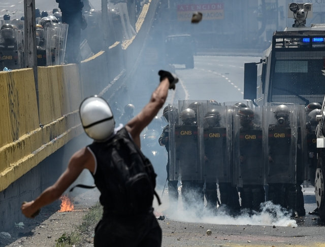 "Opposition activists clash with riot police during a protest against President Nicolas Maduro in Caracas, on May 10, 2017. Venezuelan protesters hit the streets on Wednesday armed with ""Poopootov cocktails,"" jars filled with excrement which they vowed to hurl at police as a wave of anti-government demonstrations turned dirty. / AFP PHOTO / CARLOS BECERRA"