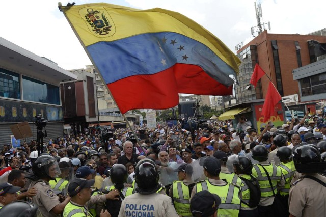 Opposition activists confront riot police during a protest against the government in Caracas on May 12, 2017. Daily clashes between demonstrators -who blame elected President Nicolas Maduro for an economic crisis that has caused food shortage- and security forces have left 38 people dead since April 1. Protesters demand early elections, accusing Maduro of repressing protesters and trying to install a dictatorship.  / AFP PHOTO / FEDERICO PARRA