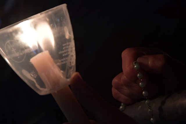 A pilgrim holds a candle and a rosary at the Shrine of Fatima during the Blessing for the Candles from the Chapel of the Apparitions by Pope Francis, in Fatima on May 12, 2017. Two of the three child shepherds who reported apparitions of the Virgin Mary in Fatima, Portugal, one century ago, will be declared saints on May 13, 2017 by Pope Francis. The canonisation of Jacinta and Francisco Marto will take place during the Argentinian pontiff's visit to a Catholic shrine visited by millions of pilgrims every year. / AFP PHOTO / Tiziana FABI