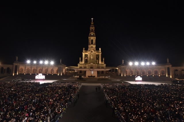 Pilgrims hold candles at the Shrine of Fatima during the Blessing for the Candles from the Chapel of the Apparitions by Pope Francis, in Fatima on May 12, 2017. Two of the three child shepherds who reported apparitions of the Virgin Mary in Fatima, Portugal, one century ago, will be declared saints on May 13, 2017 by Pope Francis. The canonisation of Jacinta and Francisco Marto will take place during the Argentinian pontiff's visit to a Catholic shrine visited by millions of pilgrims every year. / AFP PHOTO / TIZIANA FABI