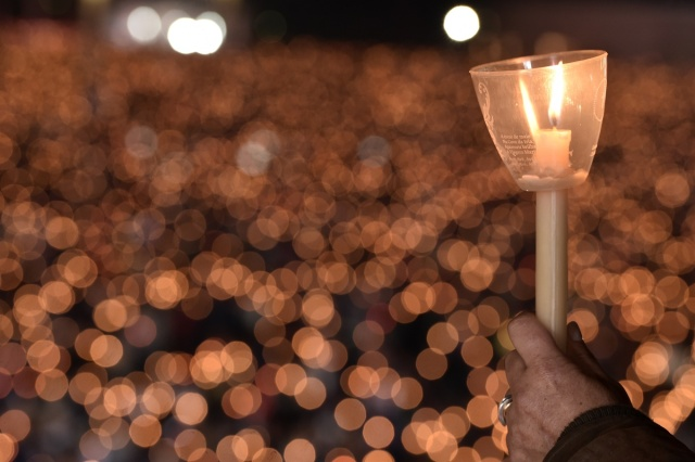 A pilgrim holds a candle at the Shrine of Fatima during the Blessing for the Candles from the Chapel of the Apparitions by Pope Francis, in Fatima on May 12, 2017. Two of the three child shepherds who reported apparitions of the Virgin Mary in Fatima, Portugal, one century ago, will be declared saints on May 13, 2017 by Pope Francis. The canonisation of Jacinta and Francisco Marto will take place during the Argentinian pontiff's visit to a Catholic shrine visited by millions of pilgrims every year. / AFP PHOTO / TIZIANA FABI