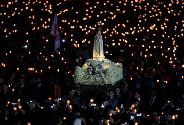 Faithful carry the statue of Our Lady of Fatima at Fatima shrine, in Fatima, on May 12, 2017. Two of the three child shepherds who reported apparitions of the Virgin Mary in Fatima, Portugal, one century ago, will be declared saints on May 13, 2017 by Pope Francis. The canonisation of Jacinta and Francisco Marto will take place during the Argentinian pontiff's visit to a Catholic shrine visited by millions of pilgrims every year. / AFP PHOTO / FRANCISCO LEONG