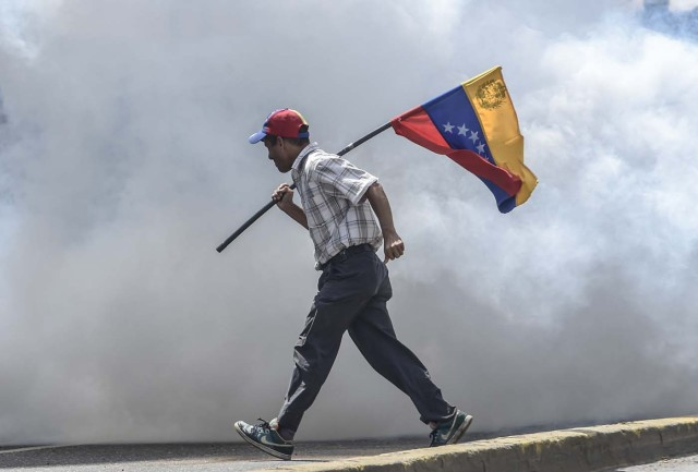An opposition demonstrator carries the national flag in clashes with the riot police during a demonstration against Venezuelan President Nicolas Maduro in Caracas, on May 26, 2017. Riot police in Venezuela fired tear gas and water cannon to stop anti-government protesters from marching on a key military installation Friday during the latest violence in nearly two months of unrest. / AFP PHOTO / JUAN BARRETO