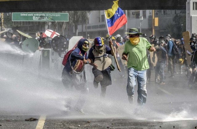 Opposition activists clash with the riot police during a demonstration against Venezuelan President Nicolas Maduro in Caracas, on May 26, 2017. Both the Venezuelan government and the opposition admit that violent protests that have gripped the country for nearly two months are out of control -- and analysts warn they could be a double-edged sword that might trigger even more unrest. / AFP PHOTO / JUAN BARRETO