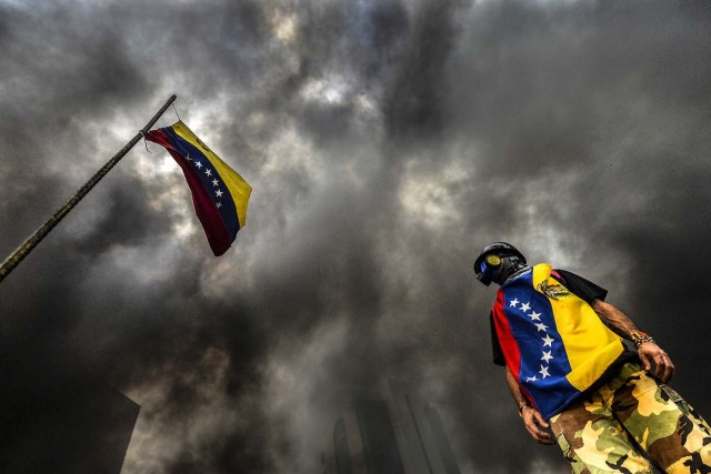 An anti-government demonstrator stands next to a national flag during an opposition protest blocking the Francisco Fajardo highway in Caracas on May 27, 2017. Demonstrations that got underway in late March have claimed the lives of 58 people, as opposition leaders seek to ramp up pressure on Venezuela's leftist president, whose already-low popularity has cratered amid ongoing shortages of food and medicines, among other economic woes. / AFP PHOTO / LUIS ROBAYO