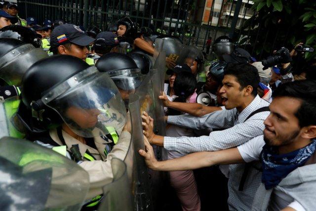 Los partidarios de la oposición se enfrentaron a las fuerzas de seguridad el viernes, mientras protestaban contra el presidente Nicolás Maduro en Caracas, Venezuela. Credit Carlos Garcia Rawlins / Reuters