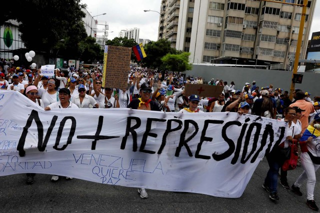 """Demonstrators hold a banner that reads """"No more repression"""" during a women's march to protest against President Nicolas Maduro's government in Caracas, Venezuela, May 6, 2017. REUTERS/Carlos Garcia Rawlins"""