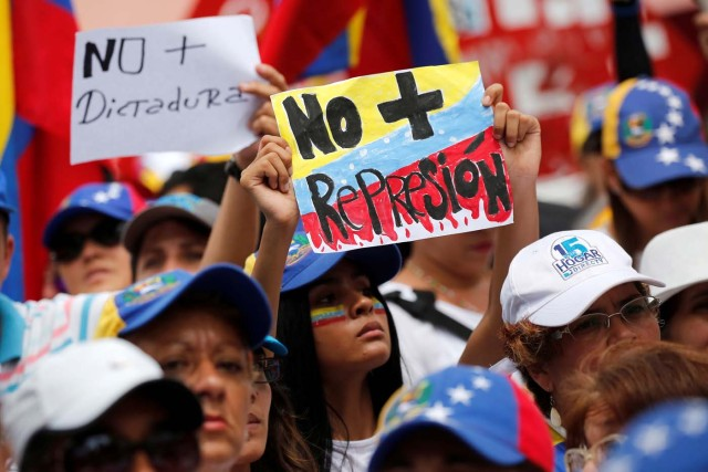 """Demonstrators hold placards that read """"No more repression"""" and """"No more dictatorship"""" during a women's march to protest against President Nicolas Maduro's government in Caracas, Venezuela, May 6, 2017. REUTERS/Carlos Garcia Rawlins"""