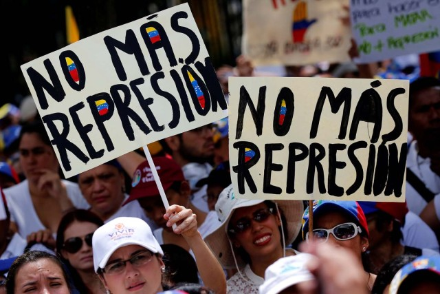 """Demonstrators hold placards that read """"No more repression"""" during a women's march to protest against President Nicolas Maduro's government in Caracas, Venezuela, May 6, 2017. REUTERS/Carlos Garcia Rawlins"""