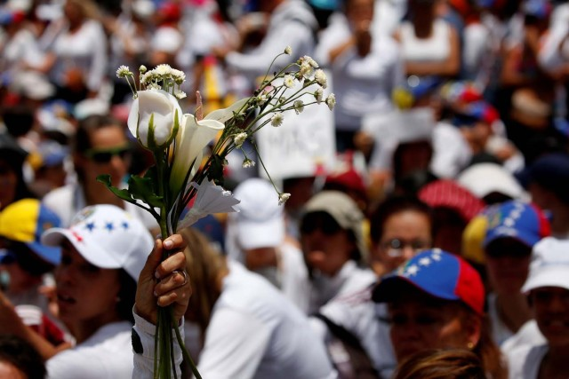 A demonstrator holds up flowers during a women's march to protest against President Nicolas Maduro's government in Caracas, Venezuela, May 6, 2017. REUTERS/Carlos Garcia Rawlins