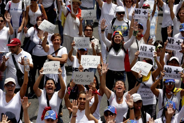 """Demonstrators hold placards that read """"No more repression"""" during a women's march to protest against President Nicolas Maduro's government in Caracas, Venezuela, May 6, 2017. REUTERS/Marco Bello"""