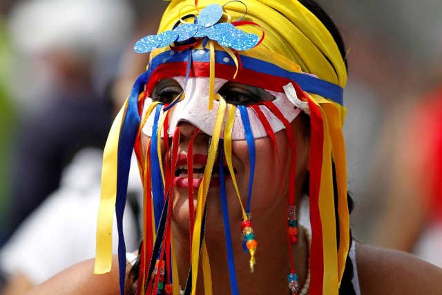 A woman wears a mask during a women's march to protest against President Nicolas Maduro's government in Caracas, Venezuela May 6, 2017. REUTERS/Christian Veron