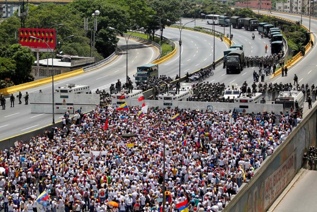 Demonstrators gather in front of the police as they attend a women's march to protest against President Nicolas Maduro's government in Caracas, Venezuela May 6, 2017. REUTERS/Christian Veron