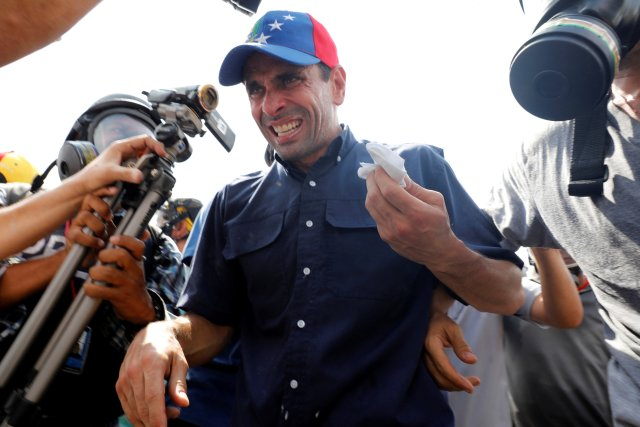 Venezuela opposition leader and Governor of Miranda state Henrique Capriles (C) reacts as he is affected by tear gas while rallying against Venezuela's President Nicolas Maduro in Caracas, Venezuela, May 10, 2017. REUTERS/Carlos Garcia Rawlins