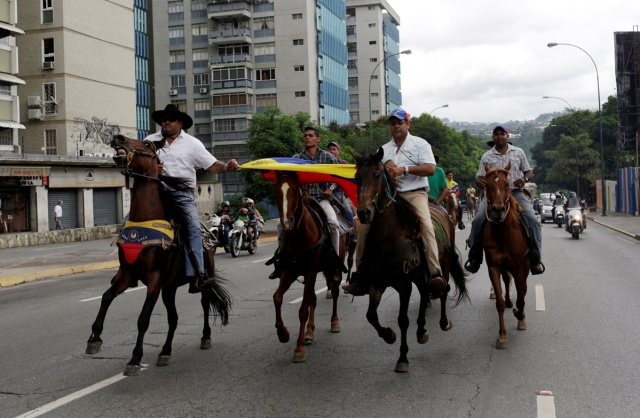 Demonstrators ride on horses and take part in a nationwide protest against President Nicolas Maduro government, in Caracas, Venezuela, May 13, 2017. REUTERS/Marco Bello