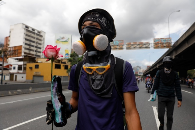 A demonstrator holds a flower during a protest against Venezuela's President Nicolas Maduro's government in Caracas, Venezuela, May 13, 2017. REUTERS/Carlos Garcia Rawlins