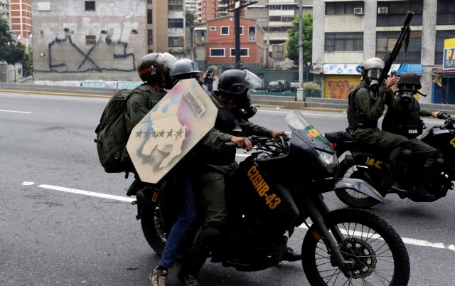 A demonstrator is detained by riot security forces during a protest against Venezuela's President Nicolas Maduro's government in Caracas, Venezuela, May 13, 2017. REUTERS/Marco Bello