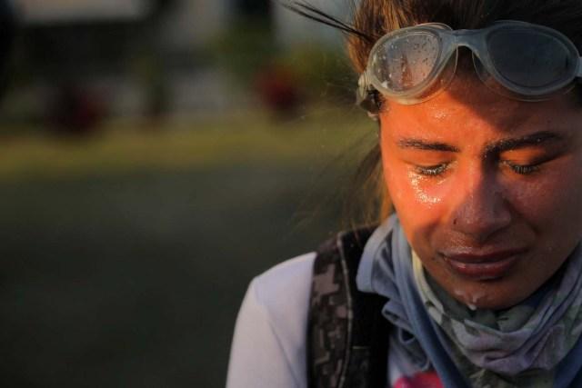 Un manifestante reacciona después de haber sido tratada por la exposición a gases lacrimógenos durante enfrentamientos con las fuerzas de seguridad antidisturbios durante una protesta contra el presidente Nicolás Maduro en Caracas, Venezuela, 18 de mayo de 2017. REUTERS/Carlos Barria TPX IMAGES OF THE DAY