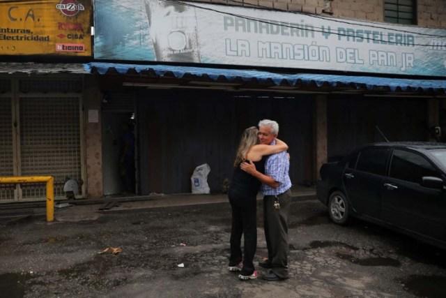 Manuel Fernandes, un comerciante, se abraza con una vecina a las afueras de su panadería luego de que fue saqueada en medio de las protestas en contra del presidente venezolano Nicolás Maduro en la ciudad de Los Teques, cerca de Caracas, Venezuela, 19 de mayo de 2017. REUTERS/Carlos Barria