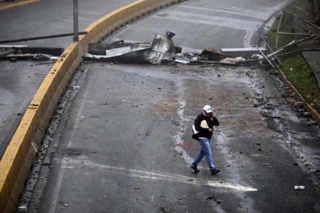 Un residente camina en medio de la barricada luego de días de protestas contra el presidente venezolano Nicolás Maduro en la ciudad de Los Teques, cerca de Caracas, Venezuela, 19 de mayo de 2017. REUTERS/Carlos Barria
