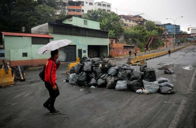 Un hombre camina al lado de la barricada luego de días de protestas contra el presidente venezolano Nicolás Maduro en la ciudad de Los Teques, cerca de Caracas, Venezuela, 19 de mayo de 2017. REUTERS/Carlos Barria