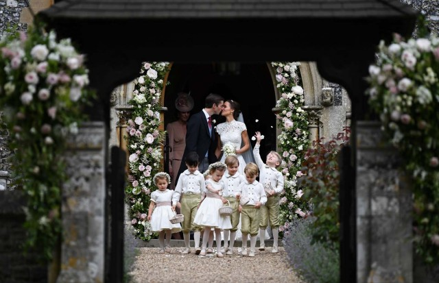 Pippa Middleton kisses her new husband James Matthews, following their wedding ceremony at St Mark's Church, as the bridesmaids, including Britain's Princess Charlotte and pageboys, including Prince George, walk ahead, in Englefield, Britain May 20, 2017. REUTERS/Justin Tallis/Pool
