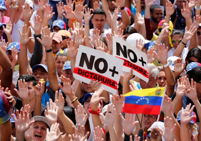 """Opposition supporters rally against President Nicolas Maduro with signs that read """"no more dictatorship"""" in Caracas, Venezuela, May 20, 2017. REUTERS/Carlos Garcia Rawlins"""