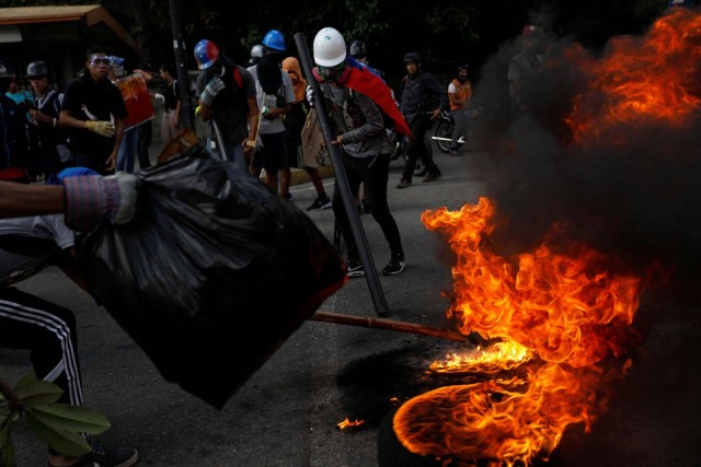 Opposition supporters build a fire barricade while rallying against President Nicolas Maduro in Caracas, Venezuela, May 20, 2017. REUTERS/Carlos Garcia Rawlins