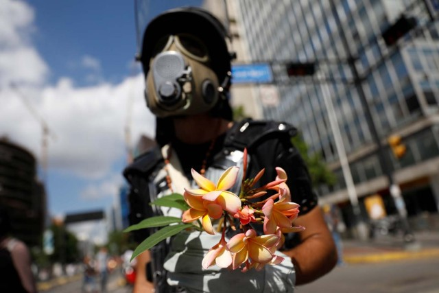 An opposition supporter holds a bouquet of flowers during a rally against Venezuela's President Nicolas Maduro in Caracas, Venezuela May 20, 2017. REUTERS/Carlos Garcia Rawlins