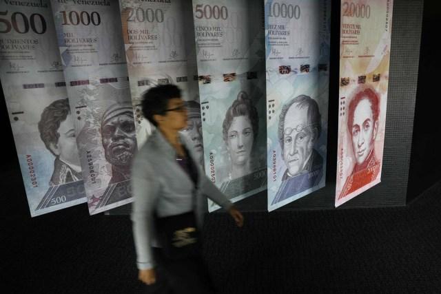 A woman walks by banners of Venezuelan bolivar notes displayed at the Venezuelan Central Bank building in Caracas, Venezuela May 23, 2017. REUTERS/Carlos Barria