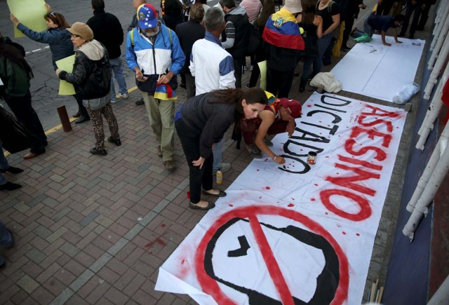"People prepare a banner that reads ""Assassin dictator"" during a protest against Venezuelan President Nicolas Maduro's visit to Ecuador to attend Ecuadorian President Lenin Moreno's inauguration, in Quito, Ecuador, May 23, 2017. REUTERS/Mariana Bazo"