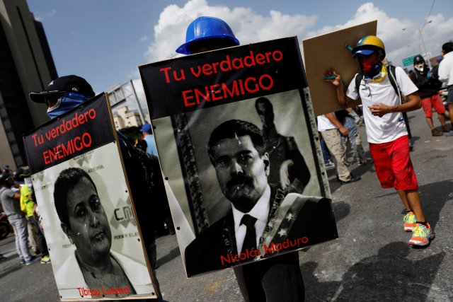 """Demonstrators carry signs with images of President Nicolas Maduro and National Electoral Council (CNE) President Tibisay Lucena with that reads """" your real enemy"""" while rallying against President Nicolas Maduro in Caracas, Venezuela, May 27, 2017. REUTERS/Carlos Garcia Rawlins"""