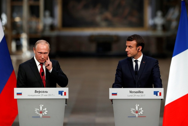 French President Emmanuel Macron (R) and Russian President Vladimir Putin (L) react during a joint press conference at the Chateau de Versailles before the opening of an exhibition marking 300 years of diplomatic ties between the two countries in Versailles, France, May 29, 2017. REUTERS/Philippe Wojazer