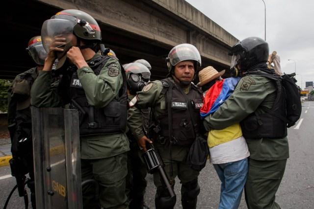 CAR012. CARACAS (VENEZUELA), 03/05/2017 - Militares retiran a una mujer que bloqueaba el paso de una tanqueta de la Guardia Nacional durante una manifestación encabezada por diputados opositores hoy, miércoles 3 de mayo de 2017, en Caracas (Venezuela). La Guardia Nacional Bolivariana (GNB, policía militarizada) de Venezuela dispersó hoy con gases lacrimógenos una movilización opositora en el este de Caracas que pretendía llegar hasta la sede de la Asamblea Nacional (AN, Parlamento), ubicada en el centro de la capital. EFE/MIGUEL GUTIERREZ