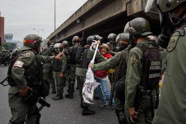 CAR014. CARACAS (VENEZUELA), 03/05/2017 - Militares retiran a una mujer (c) que bloqueaba el paso de una tanqueta de la Guardia Nacional durante una manifestación encabezada por diputados opositores hoy, miércoles 3 de mayo de 2017, en Caracas (Venezuela). La Guardia Nacional Bolivariana (GNB, policía militarizada) de Venezuela dispersó hoy con gases lacrimógenos una movilización opositora en el este de Caracas que pretendía llegar hasta la sede de la Asamblea Nacional (AN, Parlamento), ubicada en el centro de la capital. EFE/MIGUEL GUTIERREZ