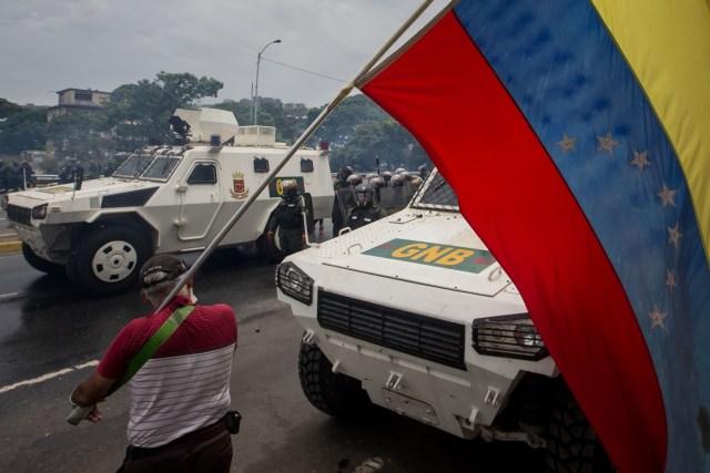 CAR020. CARACAS (VENEZUELA), 03/05/2017 - Un hombre con una bandera venezolana permanece junto a unas tanquetas de la Guardia Bolivariana durante una manifestación hoy, miércoles 3 de mayo de 2017, en Caracas (Venezuela). La Guardia Nacional Bolivariana (GNB, policía militarizada) de Venezuela dispersó hoy con gases lacrimógenos una movilización opositora en el este de Caracas que pretendía llegar hasta la sede de la Asamblea Nacional (AN, Parlamento), ubicada en el centro de la capital. EFE/MIGUEL GUTIERREZ