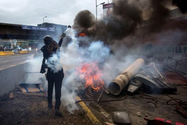 CAR028. CARACAS (VENEZUELA), 03/05/2017 - Participantes de una manifestación se enfrentan con miembros de la Guardia Bolivariana hoy, miércoles 3 de mayo de 2017, en Caracas (Venezuela). La Guardia Nacional Bolivariana (GNB, policía militarizada) de Venezuela dispersó hoy con gases lacrimógenos una movilización opositora en el este de Caracas que pretendía llegar hasta la sede de la Asamblea Nacional (AN, Parlamento), ubicada en el centro de la capital. EFE/MIGUEL GUTIERREZ