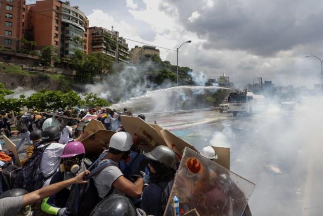 CAR46. CARACAS (VENEZUELA), 10/05/2017 - Manifestantes se enfrentan a la Guardia Nacional Bolivariana hoy, miércoles 10 de mayo de 2017, en Caracas (Venezuela). Efectivos de las fuerzas de seguridad del Estado venezolano dispersaron hoy con gas lacrimógeno la manifestación de la oposición que pretendía llegar hasta la sede del Tribunal Supremo de Justicia. EFE/CRISTIAN HERNÁNDEZ
