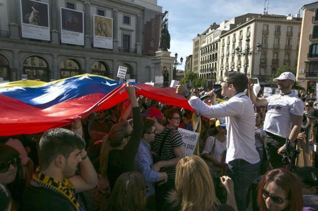 Casi un millar de opositores al gobierno venezolano se han concentrado hoy en la madrileña Plaza de Isabel II para solicitar a la comunidad internacional una mayor condena al presidente de su país Nicolás Maduro. EFE/Santi Donaire