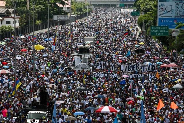 """CAR204. CARACAS (VENEZUELA), 20/05/2017 - Miles de personas participan en una en una manifestación hoy, sábado 20 de mayo de 2017, en Caracas (Venezuela). Las fuerzas de seguridad de Venezuela dispersaron hoy con gases lacrimógenos una marcha opositora que pretendía movilizarse desde el este de Caracas hasta la sede del Ministerio de Interior, en el centro de la ciudad, órgano al que los opositores responsabilizan de la """"represión"""" en las protestas. EFE/CRISTIAN HERNÁNDEZ"""