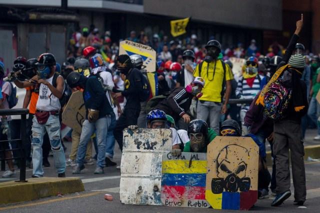 """CAR139. CARACAS (VENEZUELA), 20/05/2017.- Manifestantes opositores se enfrentan a la Policía Nacional Bolivariana hoy, sábado 20 de mayo de 2017, en Caracas (Venezuela). Las fuerzas de seguridad de Venezuela dispersaron hoy con gases lacrimógenos una marcha opositora que pretendía movilizarse desde el este de Caracas hasta la sede del Ministerio de Interior, en el centro de la ciudad, órgano al que los opositores responsabilizan de la """"represión"""" en las protestas. EFE/CRISTIAN HERNÁNDEZ"""
