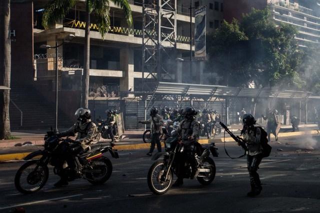 """CAR142. CARACAS (VENEZUELA), 20/05/2017.- Manifestantes opositores se enfrentan a la Policía Nacional Bolivariana hoy, sábado 20 de mayo de 2017, en Caracas (Venezuela). Las fuerzas de seguridad de Venezuela dispersaron hoy con gases lacrimógenos una marcha opositora que pretendía movilizarse desde el este de Caracas hasta la sede del Ministerio de Interior, en el centro de la ciudad, órgano al que los opositores responsabilizan de la """"represión"""" en las protestas. EFE/MIGUEL GUTIÉRREZ"""