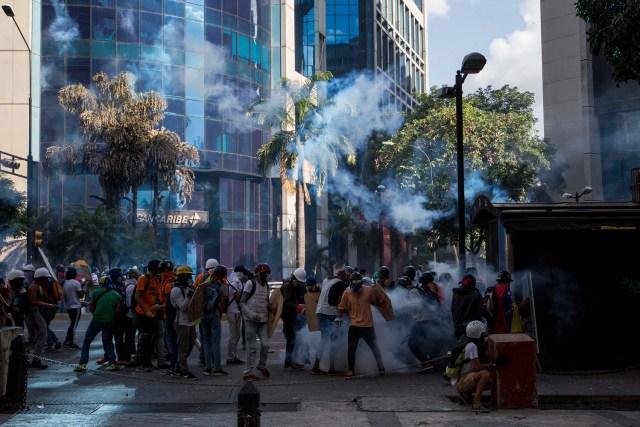 """CAR150. CARACAS (VENEZUELA), 20/05/2017.- Manifestantes opositores se enfrentan a la Policía Nacional Bolivariana hoy, sábado 20 de mayo de 2017, en Caracas (Venezuela). Las fuerzas de seguridad de Venezuela dispersaron hoy con gases lacrimógenos una marcha opositora que pretendía movilizarse desde el este de Caracas hasta la sede del Ministerio de Interior, en el centro de la ciudad, órgano al que los opositores responsabilizan de la """"represión"""" en las protestas. EFE/MIGUEL GUTIÉRREZ"""