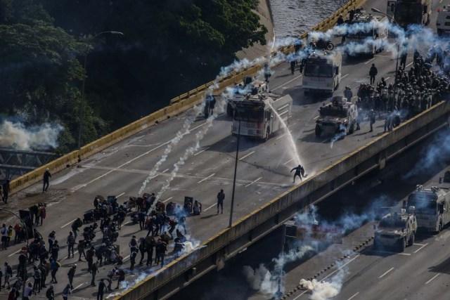 """CAR274 - CARACAS (VENEZUELA) - 27/05/2017 - Enfrentamientos entre la Guardia Nacional Bolivariana (GNB) y manifestantes opositores hoy, sábado 27 de mayo de 2017, en Caracas (Venezuela). La concentración opositora que se realizó hoy en la capital para recordar los 10 años de la salida del aire del canal privado Radio Caracas Televisión (RCTV) culminó en medio de una situación de """"tensión"""" y humo, luego de que se registraran en una autopista cercana choques entre la policía y manifestantes. EFE/CRISTIAN HERNÁNDEZ"""