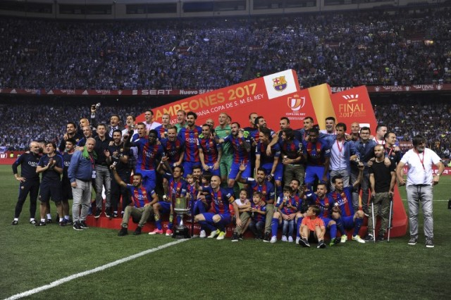 Barcelona players and staff pose with the trophy at the end of the Spanish Copa del Rey (King's Cup) final football match FC Barcelona vs Deportivo Alaves at the Vicente Calderon stadium in Madrid on May 27, 2017. Barcelona won 3-1. / AFP PHOTO / Josep LAGO