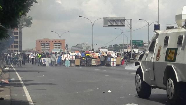 Manifestantes con escudos frente a tanqueta que reprime movilización / Foto: Eduardo Ríos