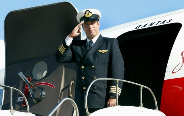 """(FILES) A file photo taken on July 12, 2002, shows Hollywood star and Qantas """"Ambassador-at-Large"""" John Travolta, standing in front of his Boeing 707 at Sydney Airport. Travolta has donated his """"beloved"""" Boeing 707 plane to an Australian aviation museum and is aiming to be part of the crew to deliver the vintage aircraft down under. Made for Qantas Airways in 1964, Travolta acquired the Boeing 707 long after Australia's national carrier retired the jet. / AFP PHOTO / Greg Wood"""