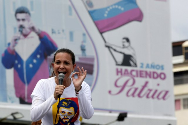 """Venezuelan opposition leader Maria Corina Machado speaks in front of a billboard with a picture of Venezuela's President Nicolas Maduro during a rally against him in Caracas, Venezuela April 24, 2017. The billboard reads, """"2 years making homeland"""". REUTERS/Marco Bello"""