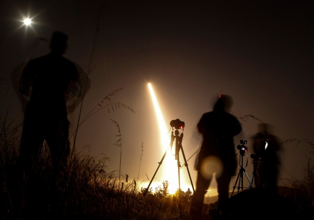Photographers take pictures of a streak of light trailing off into the night sky as the US military test fires an unarmed intercontinental ballistic missile (ICBM) at Vandenberg Air Force Base, some 130 miles (209 kms) northwest of Los Angeles, California early on May 3, 2017. / AFP PHOTO / RINGO CHIU
